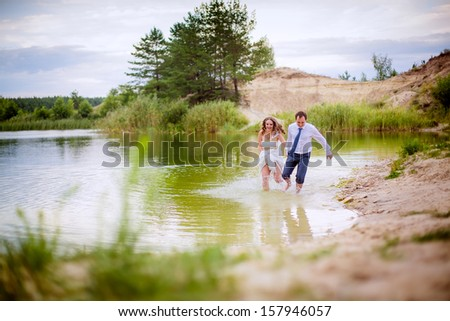 happy couple running along the water on the lake