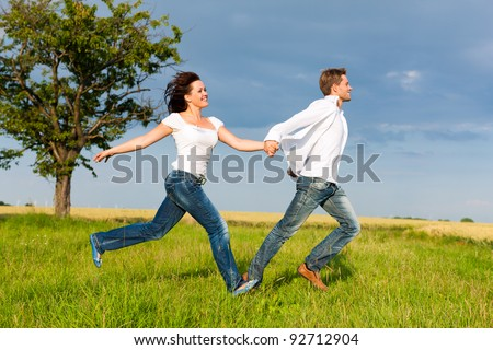 Happy couple running on a meadow in summer holding each others hands