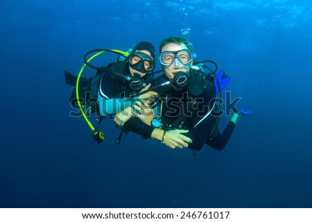 Happy couple scuba diving together