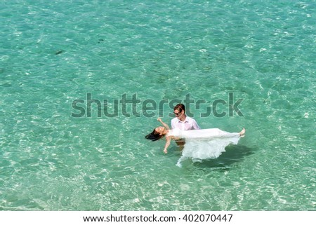Happy couple swims after wedding in turquoise sea