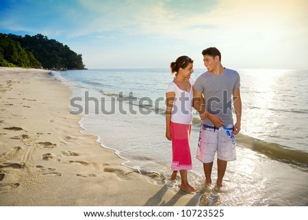 happy couple walking along a romantic sunset beach