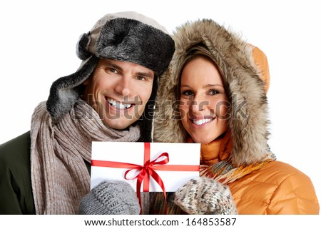 Happy couple with christmas present isolated over white background.