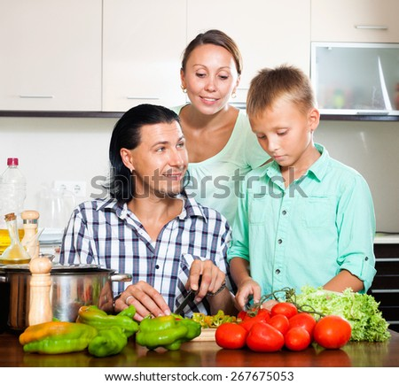 Happy couple with teenager child cutting the vegetables for salad in home kitchen