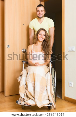 Happy couple with woman in wheelchair near apartment entrance