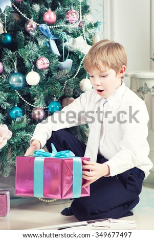 Happy cute boy with christmas tree and gifts