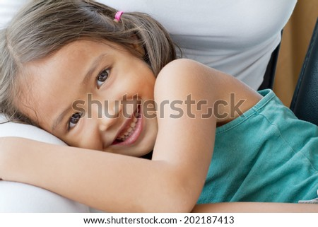 happy, cute, smiling female child, daughter playing on her mother's lap