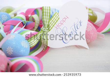 Happy Easter background with pink, blue and green ornament eggs and ribbon on vintage style rustic distressed white shabby chic wood table, with copy space for your text here, with greeting tag.