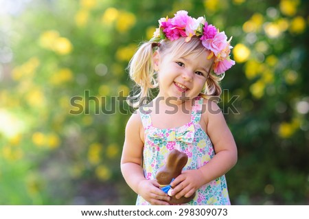 happy easter girl eat chocolate bunny at meadow background