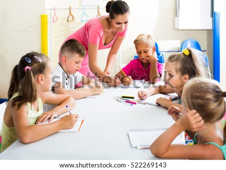 happy european children making writing exercises with help of teacher in class