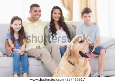 Happy family and dog watching TV together in living room