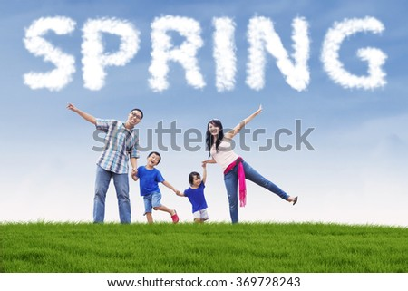 Happy family enjoy freedom while holding hands on the field under a spring cloud