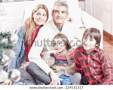 Happy family enjoying Christmas tree.