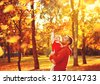 Happy family father and child daughter on a walk in the autumn leaf fall in park - stock photo