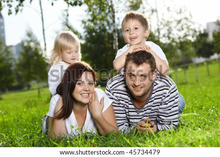 Happy family from four persons lies on a summer lawn