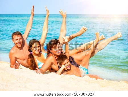 Happy Family Having Fun at the Beach. Joyful Big Family. Vacation and Travel concept. Summer Holidays. Parents with Children enjoying a holiday at the sea