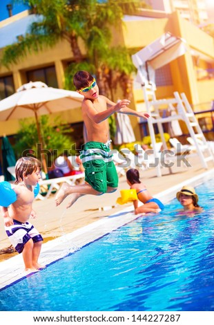 Stock photo happy family having fun in the pool son jumping into the