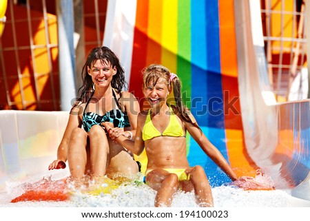 Happy family  in bikini sliding water park.