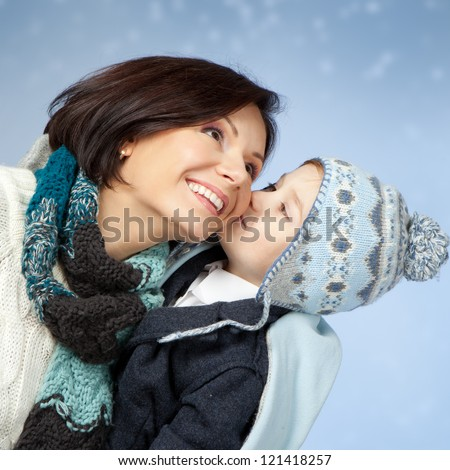 Happy family in winter clothing. Little son kissing his happy smiling mother on a cheek over blue