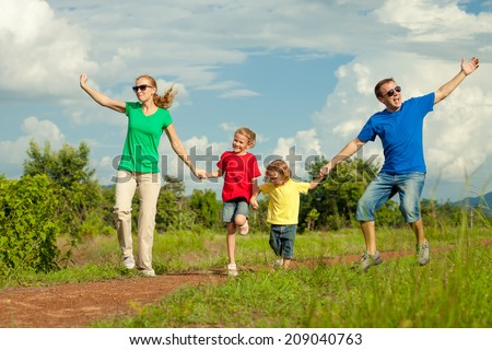 Happy family jumping on the road at the day time. Concept of friendly family.