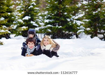 Happy family lying on the snow in winter forest, looking at the camera, horizontal photo