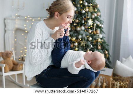 happy family mother and baby little son playing home on Christmas holidays. New Year's holidays. Toddler with mom in the festively decorated room with Christmas tree. Portrait of mother and baby boy