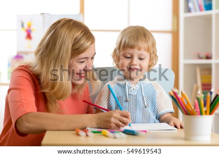 Happy family - mother and son toddler together paint. Adult woman helping to child boy.