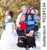 happy family: mother, father and son making a snowman outdoor on a warm winter day (focus on the  man) - stock photo