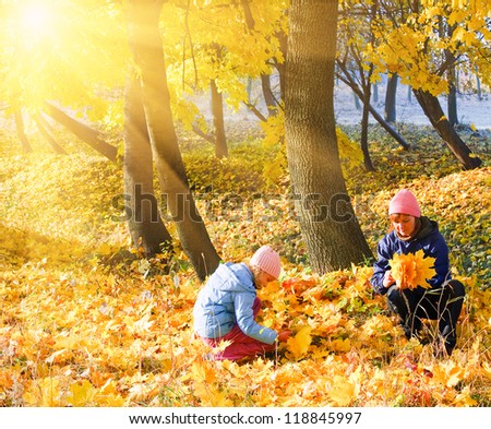 Happy family (mother with daughter) in golden evening maple autumn park and sunshine behind the tree foliage