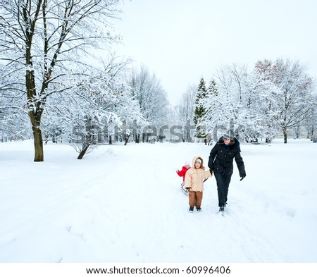 Happy family (mother with small boy and girl) in winter city park