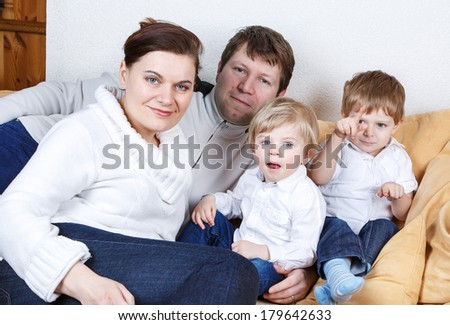 Happy family of a four having fun at home. In blue jeans and white shirts