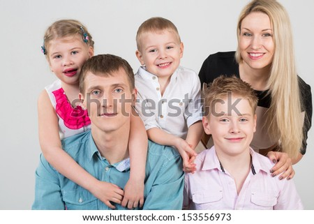 Happy family of five people, daughter hugging father in the studio