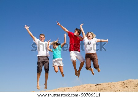 happy family of four jumping with bright blue sky at background