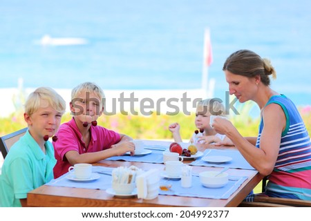 Happy family of four, mother with three kids, enjoying summer vacation eating healthy breakfast in the sea view restaurant on tropical resort. Selective focus on one of the boys.