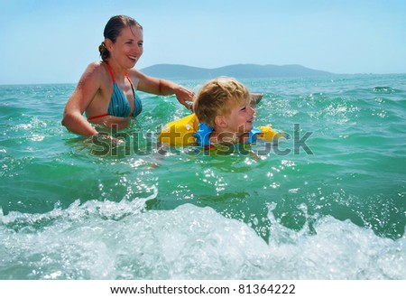 happy family of mother with kid in the waves on the sea beach