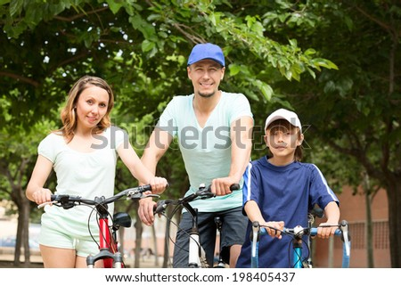 Happy family of three cycling through city in summer day
