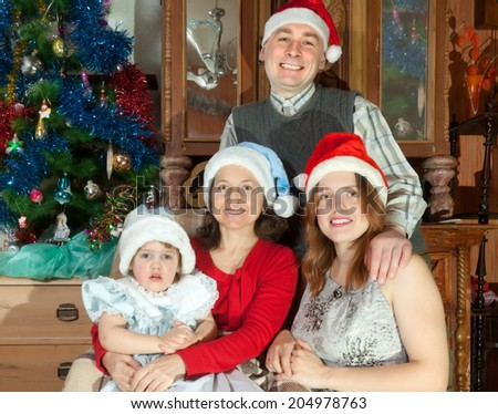 Happy family of three generations in Santa hats celebrating Christmas in living room