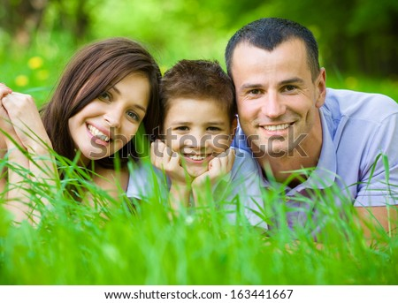 Happy family of three lying on grass. Concept of happy family relations and carefree leisure time