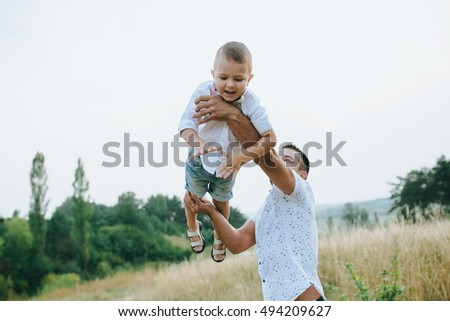 Happy family of three playing and laughing while sitting on grass outdoors, beatuful forest