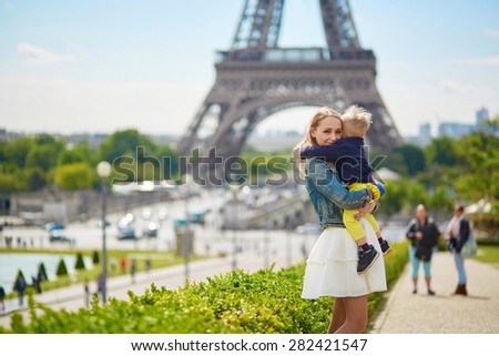 Happy family of two having fun together in Paris near the Eiffel tower