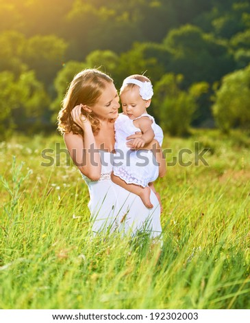 happy family on nature outdoors mother and baby daughter on the green meadow in a white dress