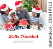 Happy family opening Christmas presents against feliz navidad - stock photo