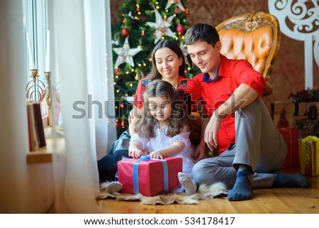 happy family opens gifts, sitting on a floor near a window. On a background the Christmas tree. Waiting for the Holiday.