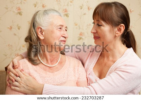 Happy family. Portrait of elderly woman and adult daughter happily looking at camera. Senior  woman with their caregiver at home.