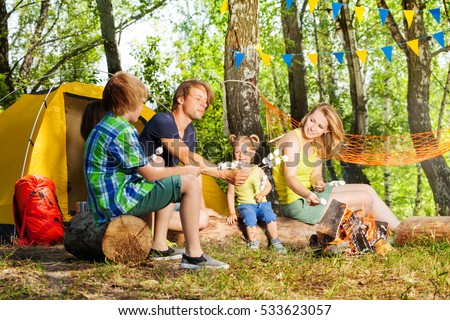 Happy family roasting marshmallow over campfire