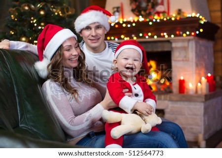 Happy family sitting on couch in front of fireplace in festive Christmas room