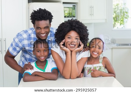 Happy family smiling at camera at home in the kitchen