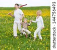 happy family walking over green field with a spade - stock photo