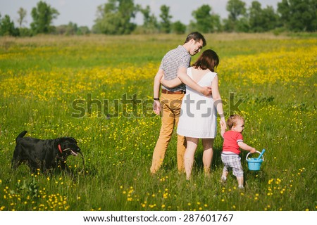 Happy family walking with black labrador dog in summer field. Father, mother, son holding hands. Family lifestyle. Togetherness. Child playing with parents and dog outside. Summer or spring day.