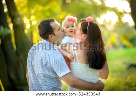 happy family walks in the park, embrace and together kiss the daughter, on a background a bright sunset