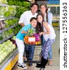 Happy family with a shopping trolley at the supermarket - stock photo
